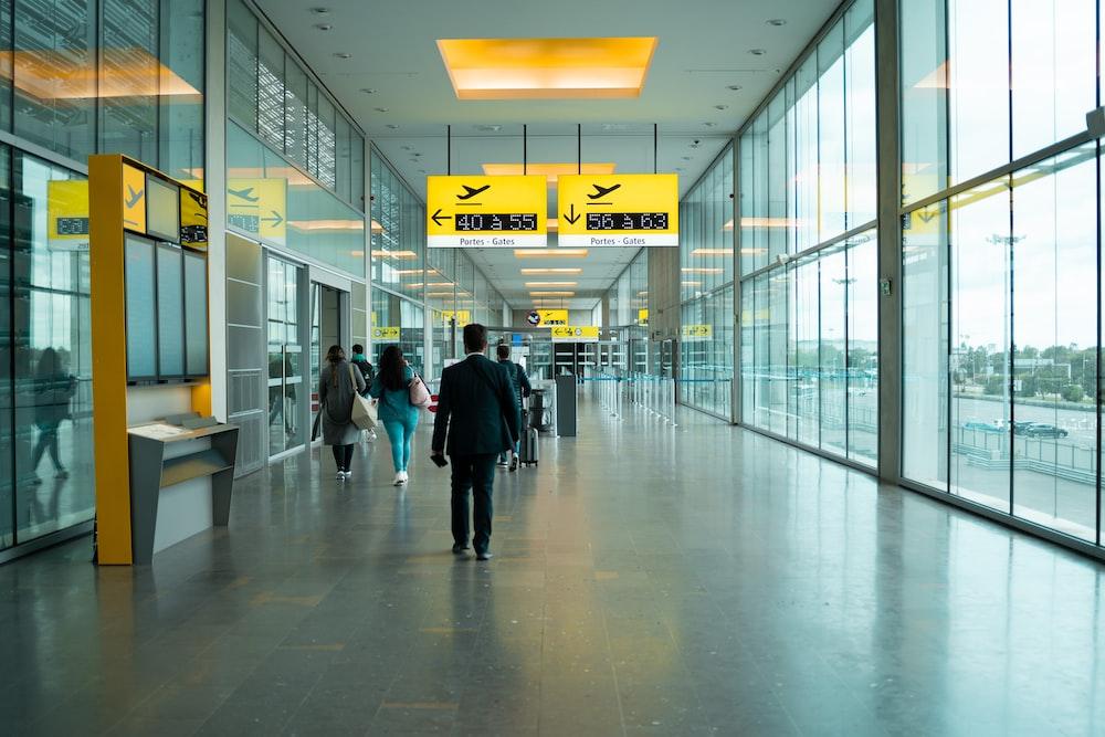 man in black jacket walking on hallway