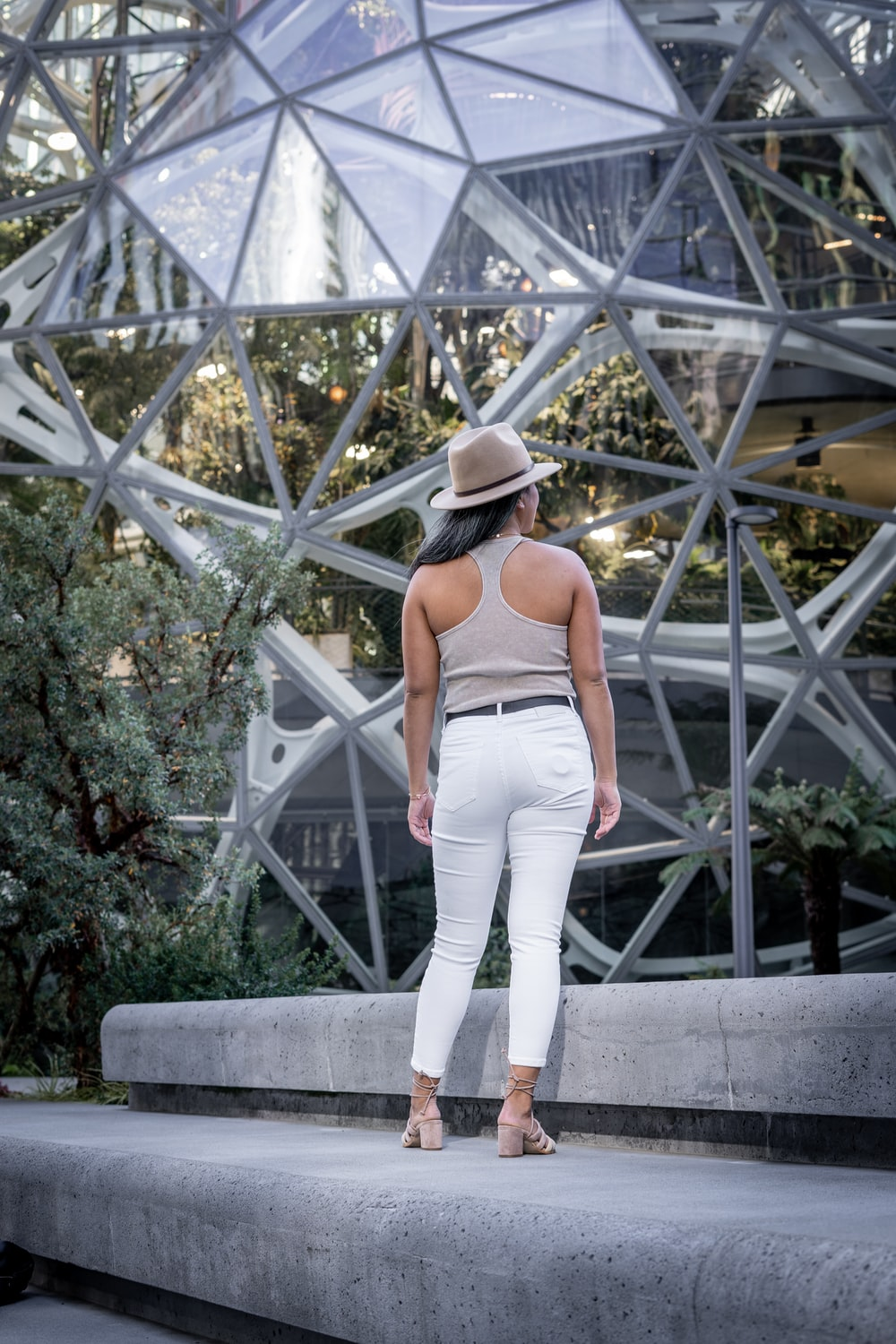 woman in gray tank top and white pants wearing black fedora hat standing on gray concrete
