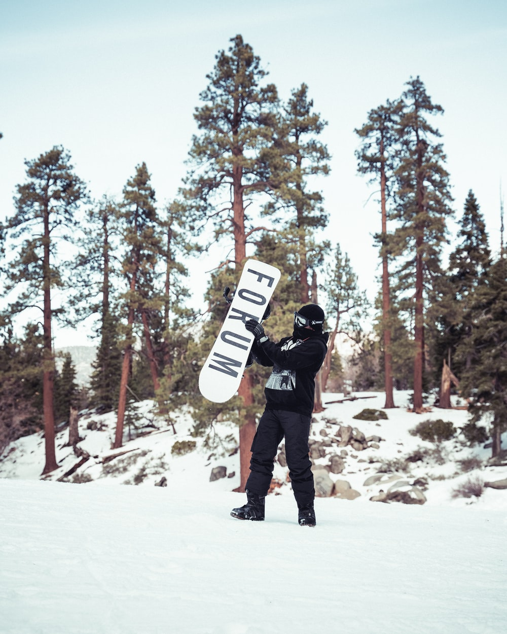 man in black jacket and black pants carrying white and black snowboard on snow covered ground