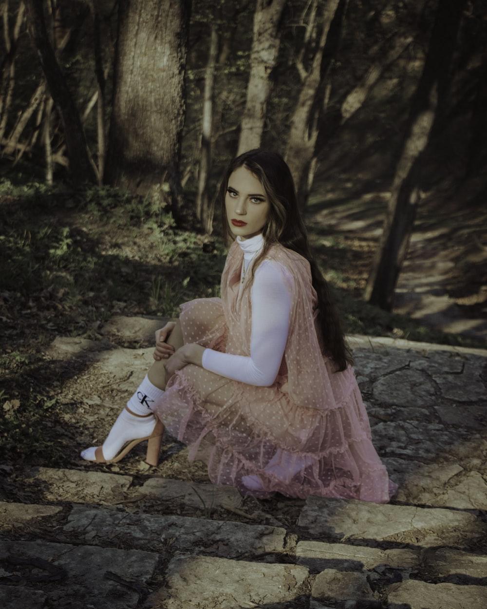 girl in pink dress sitting on brown rock