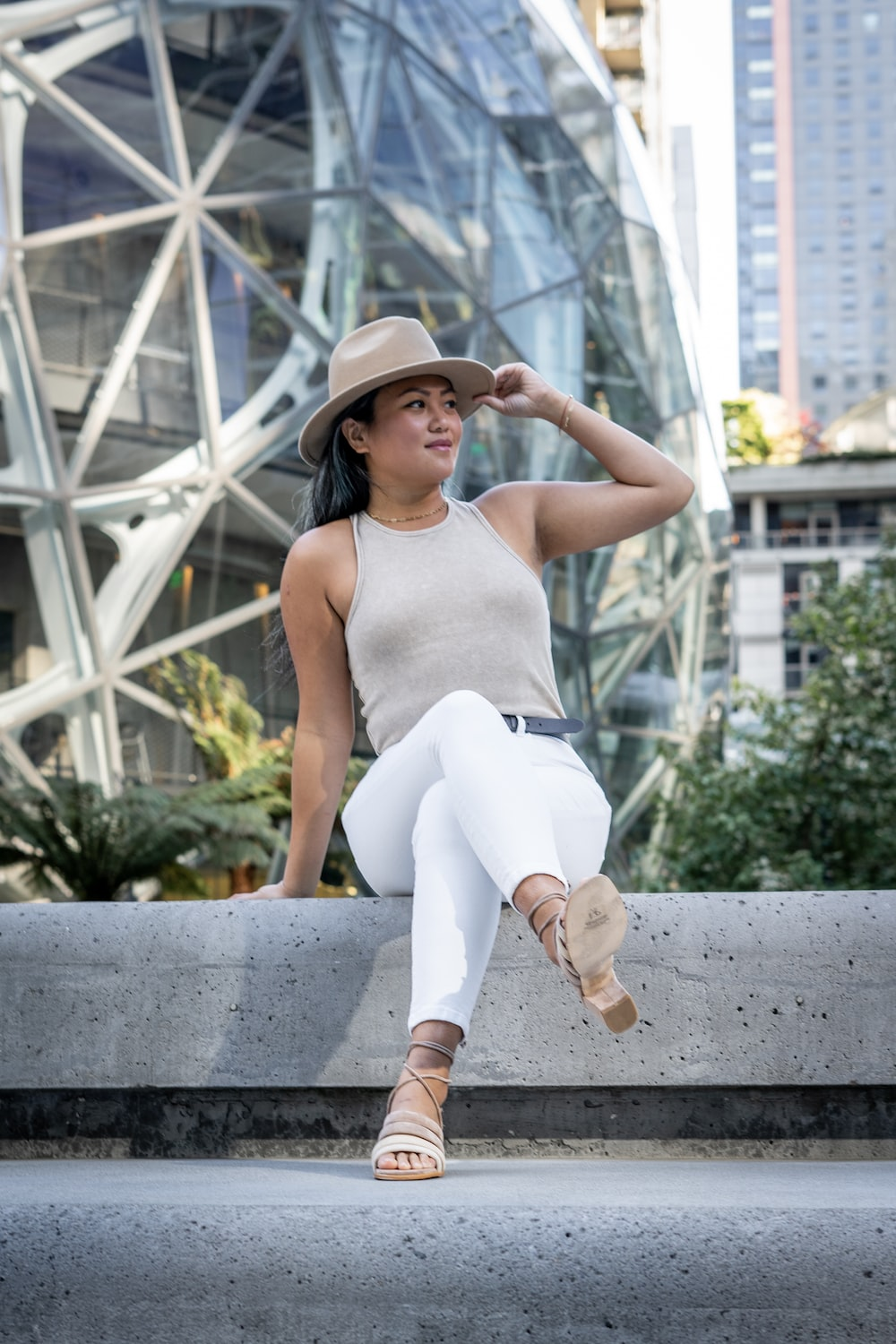 woman in white tank top and white pants sitting on concrete bench during daytime
