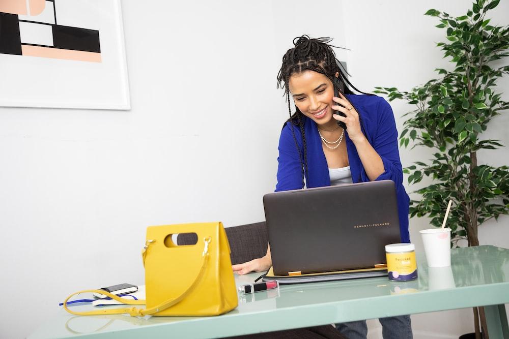 黒のラップトップコンピューターの前に座っている青い長袖シャツの女性