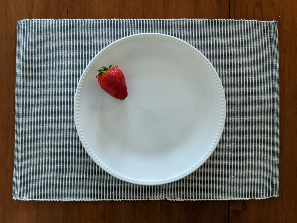 red strawberry on white ceramic plate