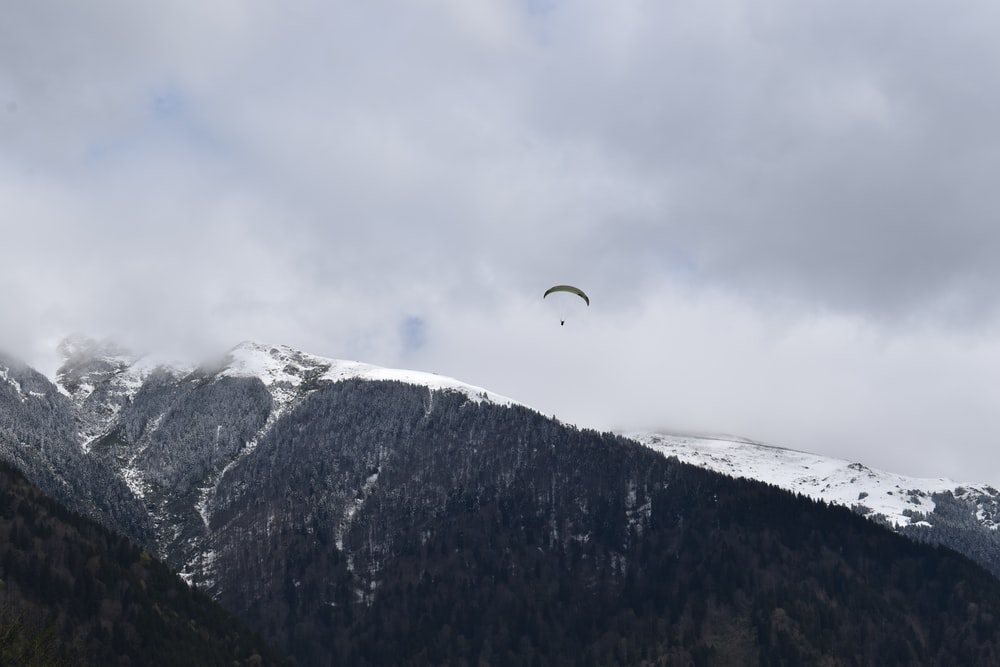 person riding parachute over snow covered mountain during daytime
