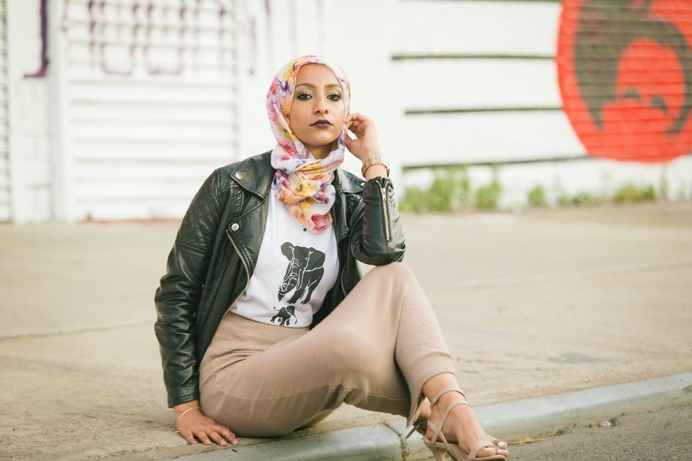 woman in black leather jacket sitting on concrete floor during daytime