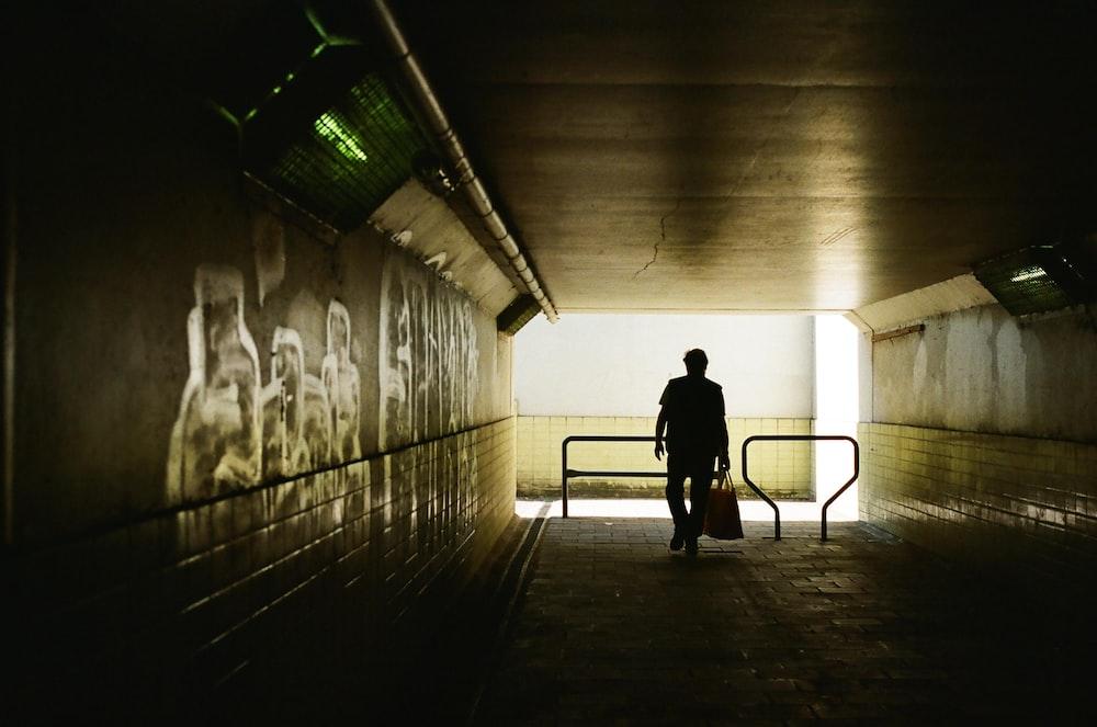 silhouette of man walking on hallway