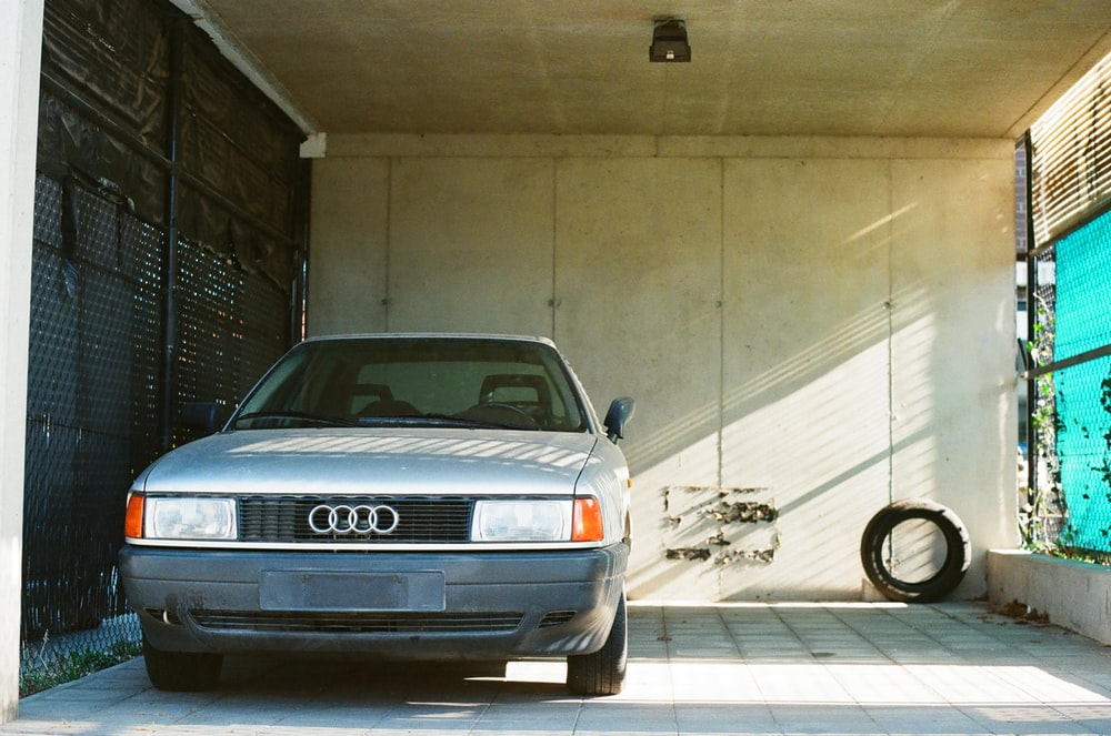 silver audi a 4 coupe parked beside brown wall