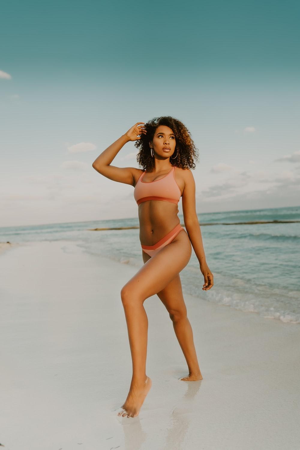 woman in red bikini standing on beach during daytime