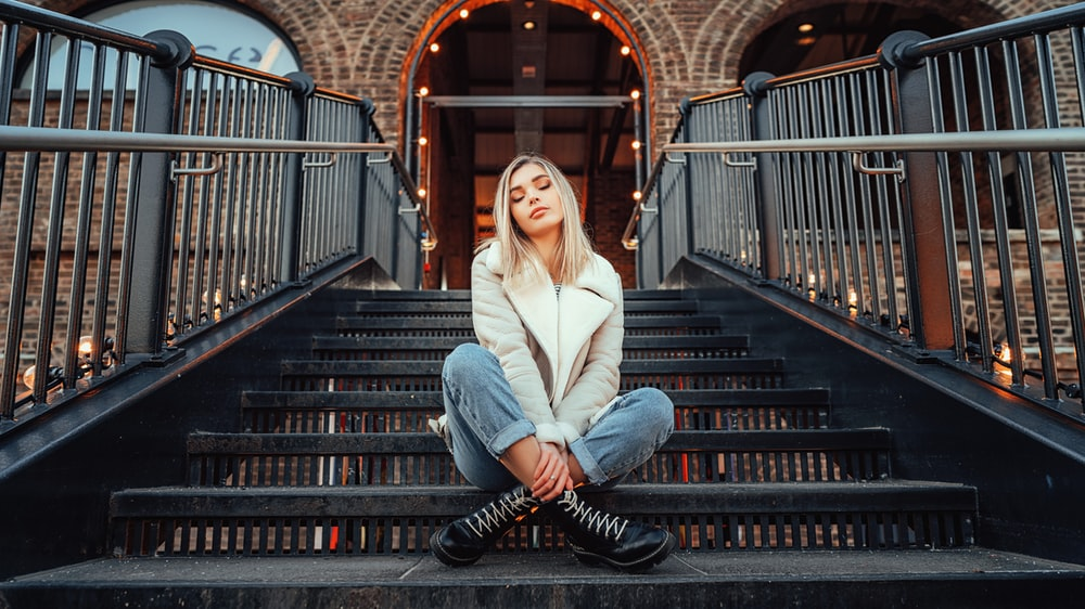 woman in white coat sitting on black staircase