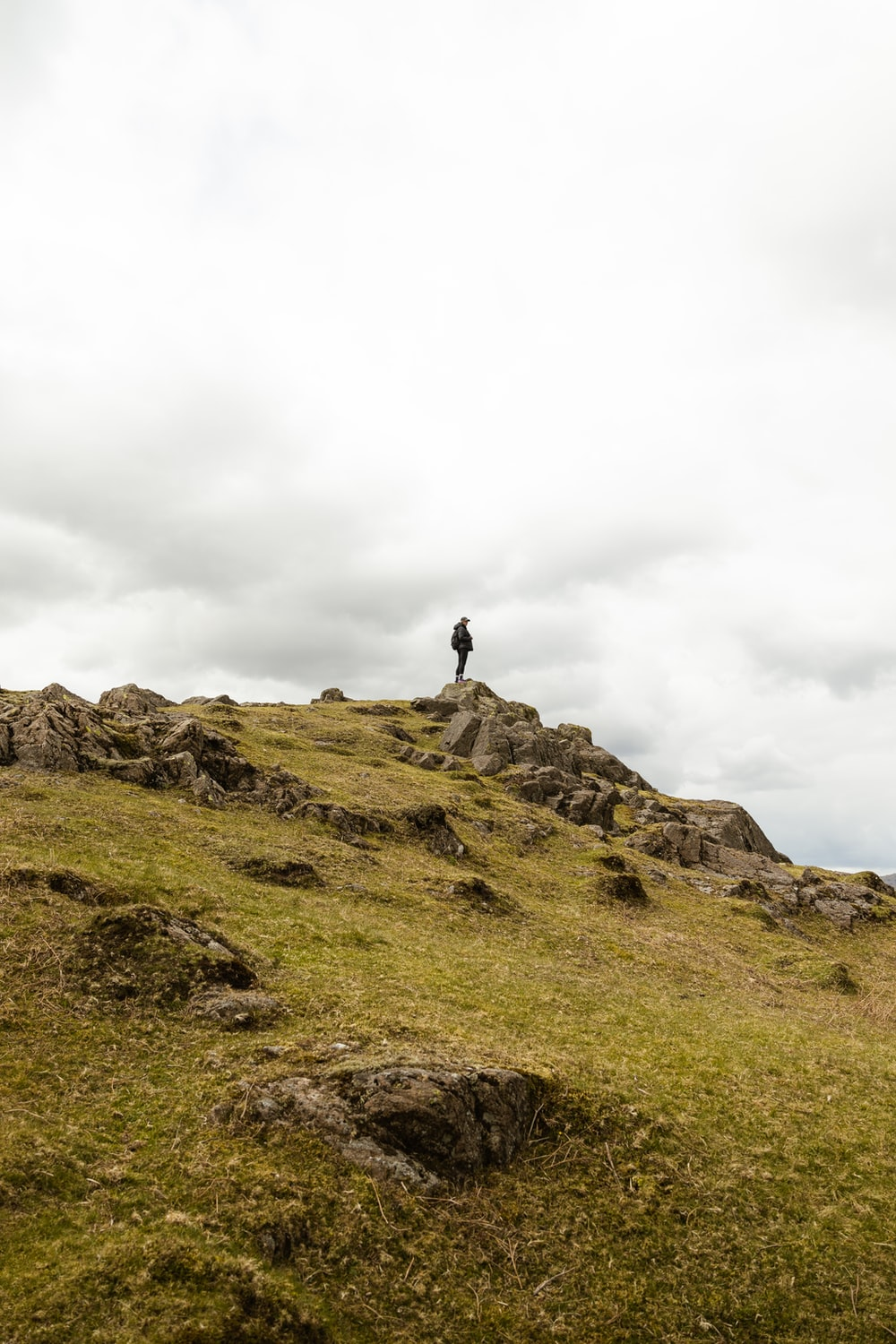 person standing on rock formation under white sky during daytime