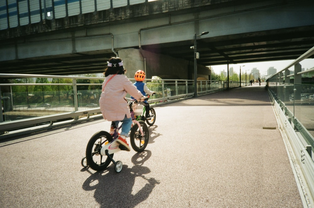 man in white jacket riding on bicycle during daytime
