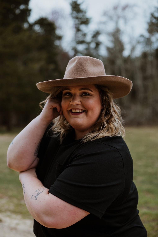 woman in black sleeveless dress wearing brown fedora hat