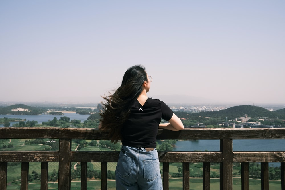 woman in black t-shirt and blue denim jeans standing on brown wooden fence during daytime