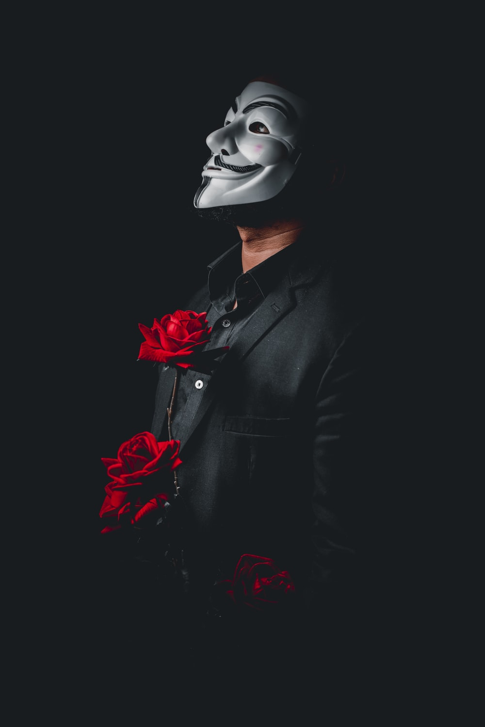 person in black suit with red rose on ear