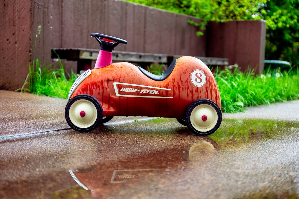 red and black ride on toy car on gray concrete floor