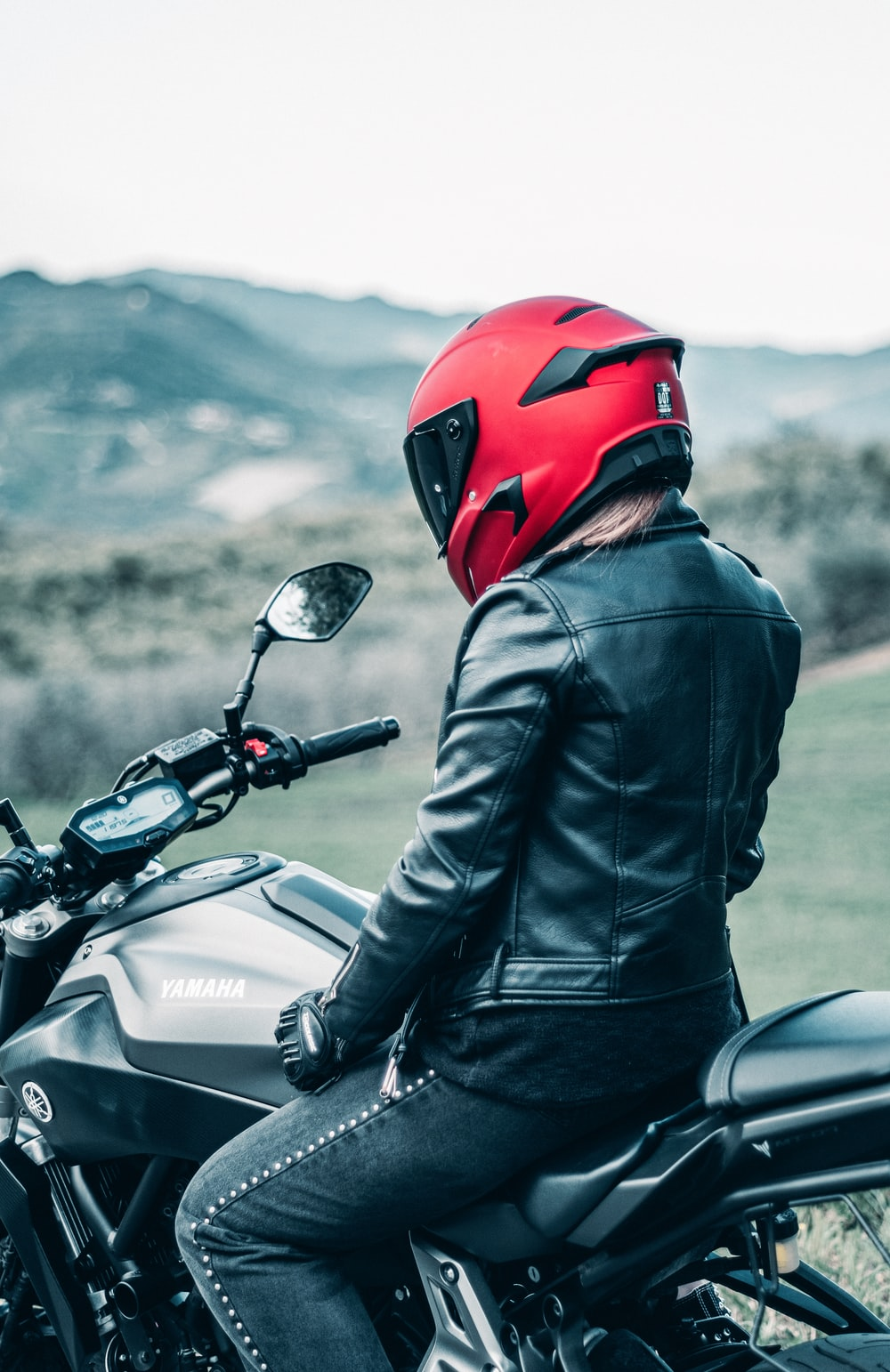 man in black leather jacket wearing red helmet riding black honda motorcycle
