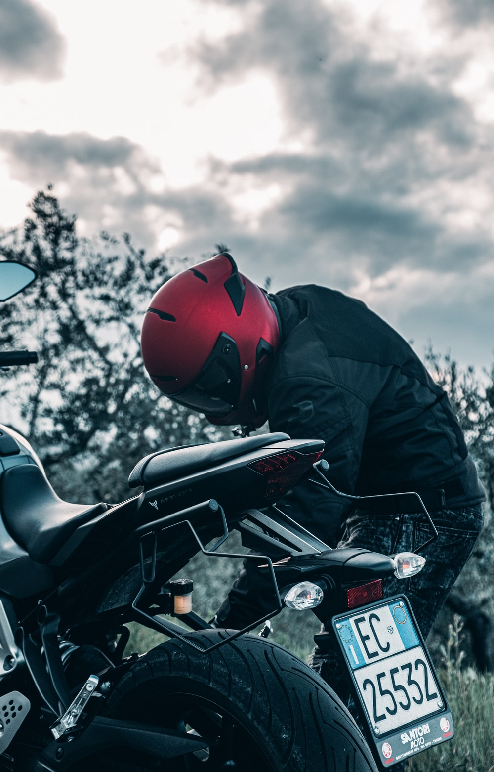 man in black jacket and red helmet riding motorcycle