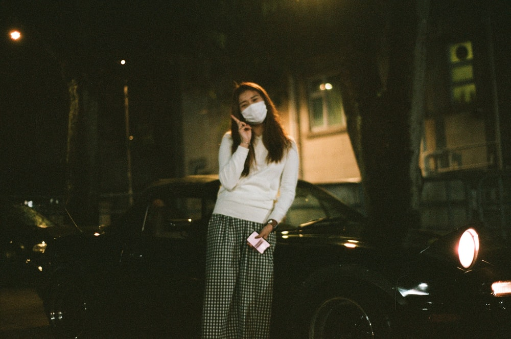 woman in white long sleeve shirt and black and white striped skirt standing beside black car