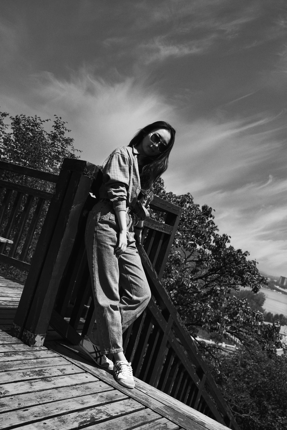 grayscale photo of person in hoodie and pants standing on wooden dock