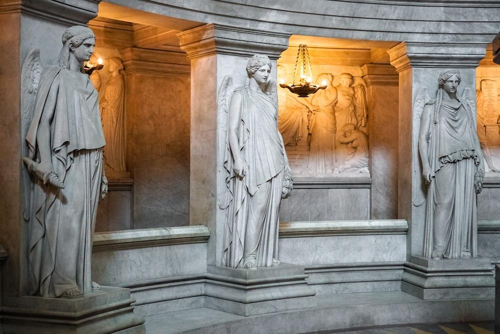 man in white robe standing beside concrete statue