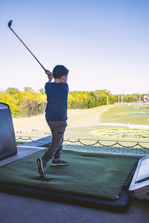 man in blue shirt and black pants holding golf club