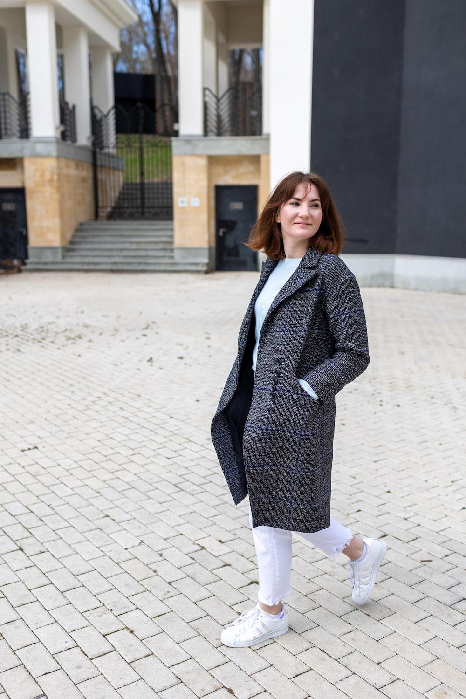 woman in blue blazer standing on sidewalk during daytime