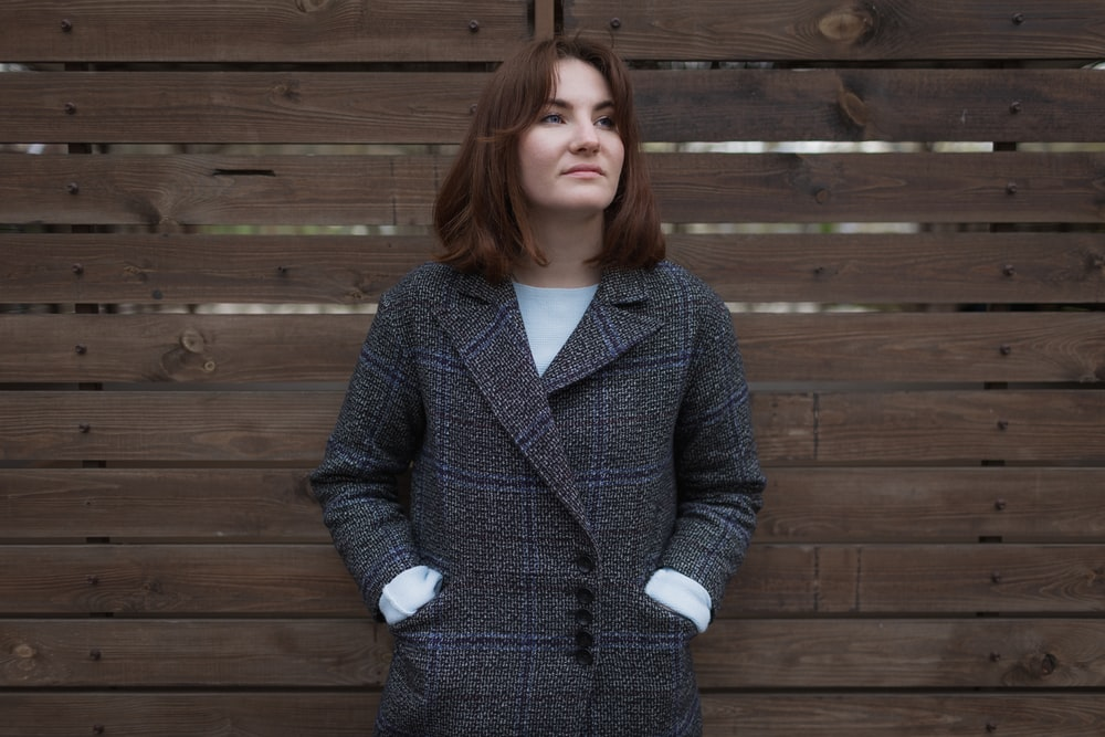 woman in blue and white polka dot coat standing near brown wooden wall