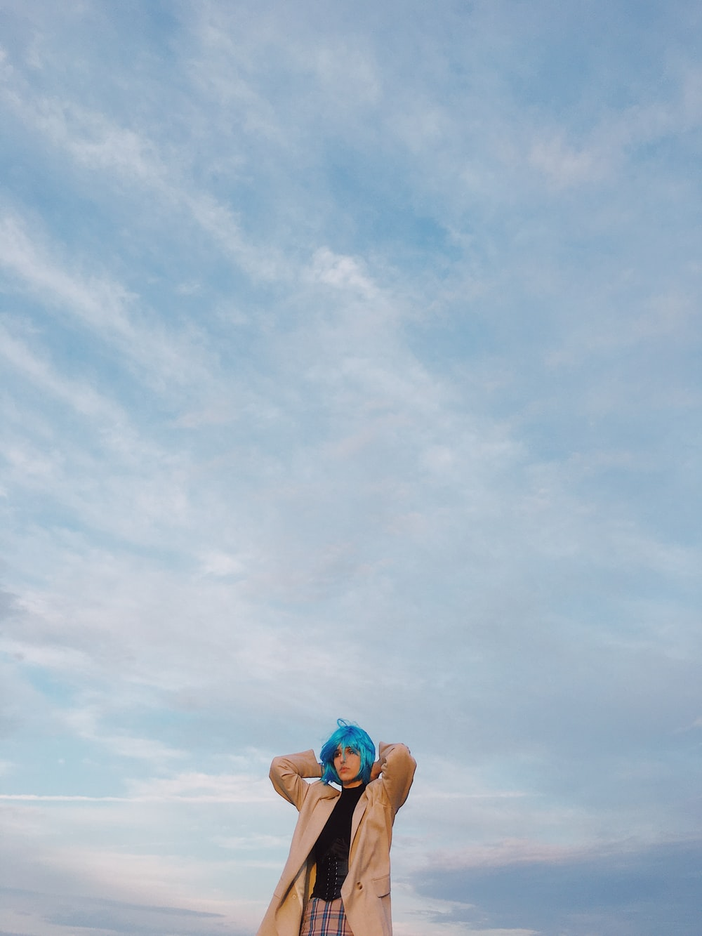 woman in blue bikini top and blue denim daisy dukes sitting on beach during daytime