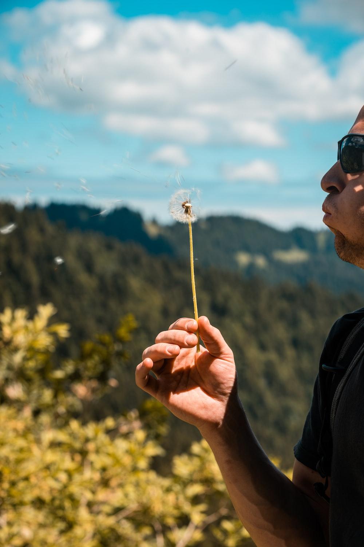 man in black jacket holding white dandelion flower during daytime