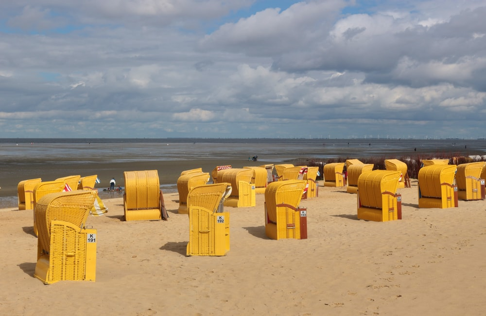 yellow plastic trash bins on brown sand under white clouds during daytime