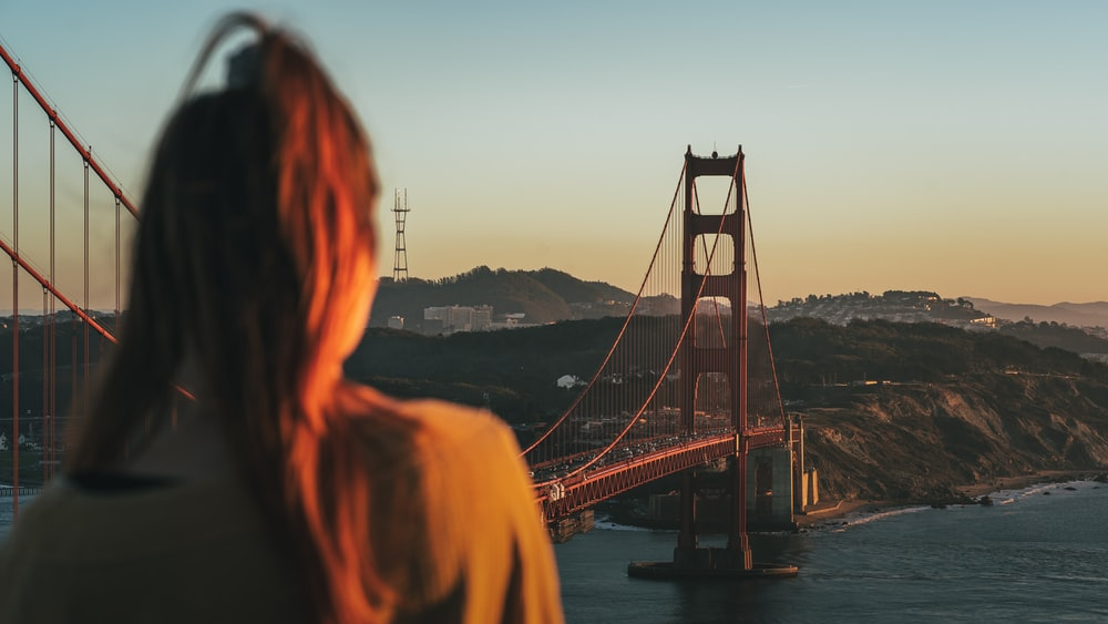 woman standing on bridge during sunset