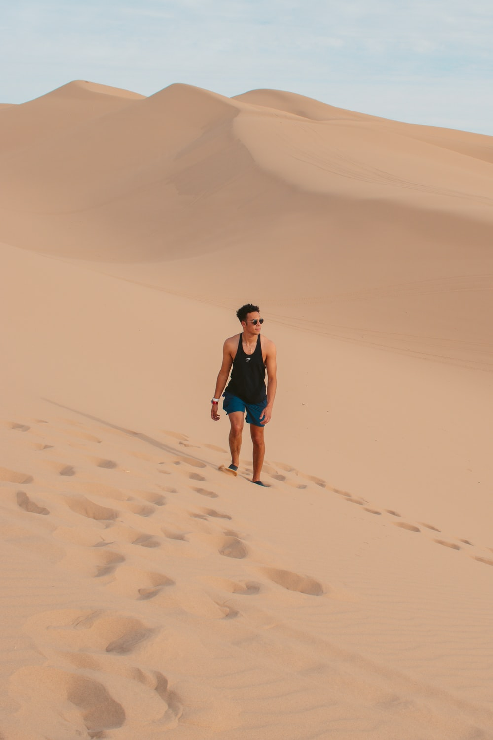 woman in blue tank top and black shorts walking on sand during daytime