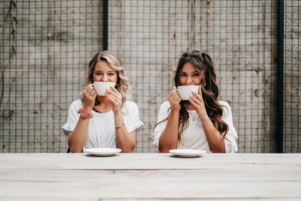 woman in white shirt drinking from white ceramic mug