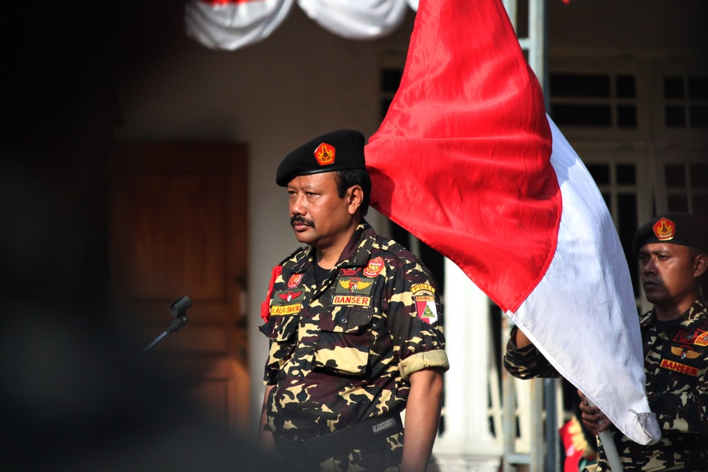 man in black and brown camouflage uniform holding red textile