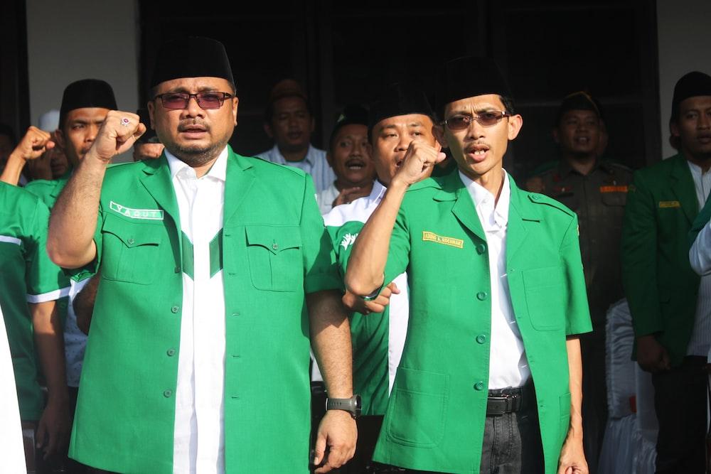 man in green button up shirt standing beside man in green button up shirt