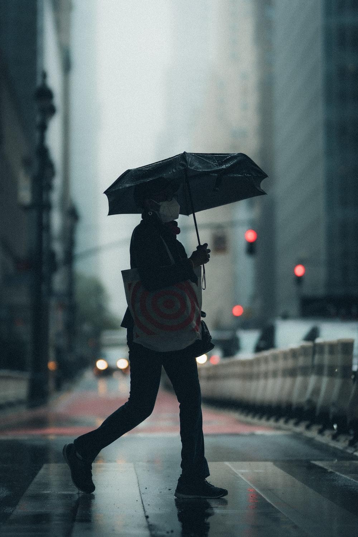 person in black jacket holding umbrella