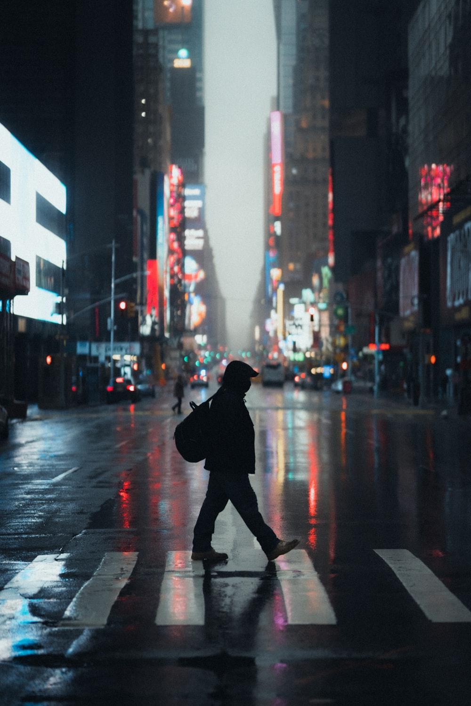 man in black hoodie walking on street during daytime