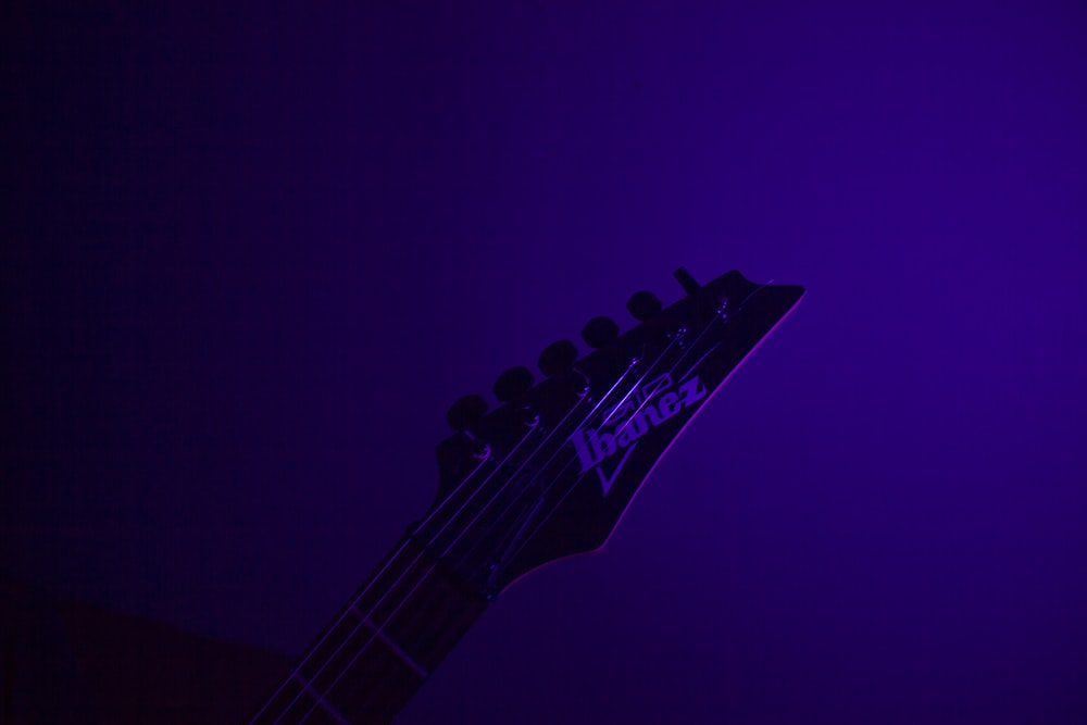 black electric guitar on purple background