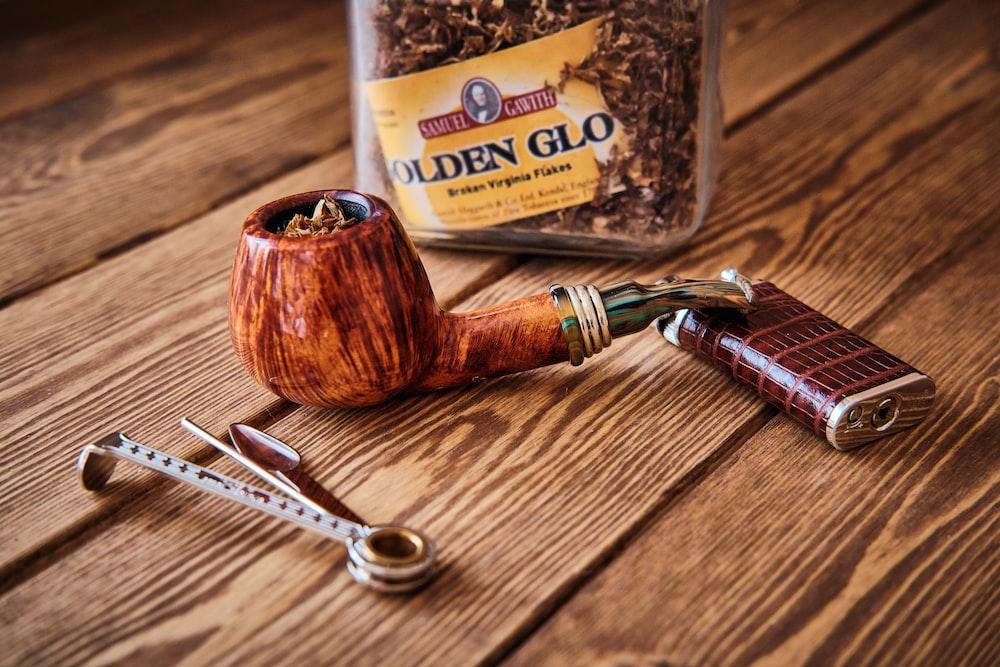 brown wooden smoking pipe beside silver scissors