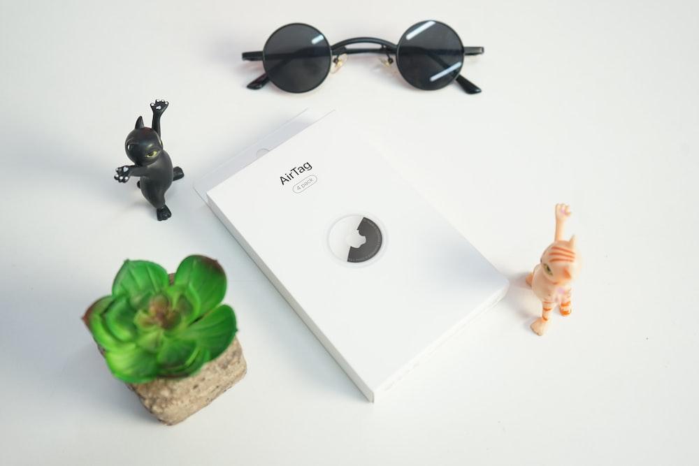 black framed sunglasses on white wooden table