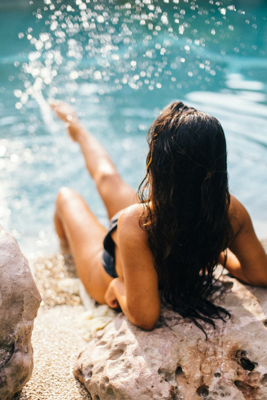 woman in black bikini lying on white sand near body of water during daytime