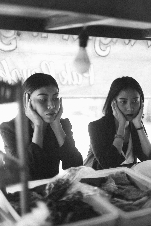 woman in black long sleeve shirt sitting beside woman in black long sleeve shirt