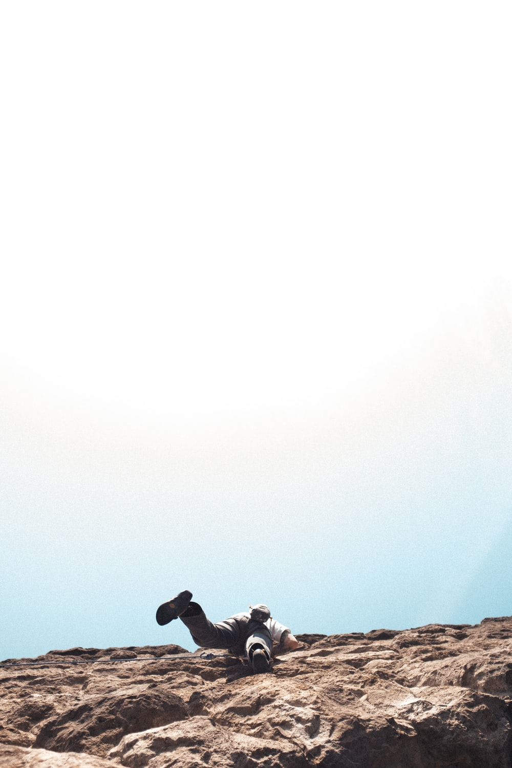 silhouette of man sitting on rock formation during daytime