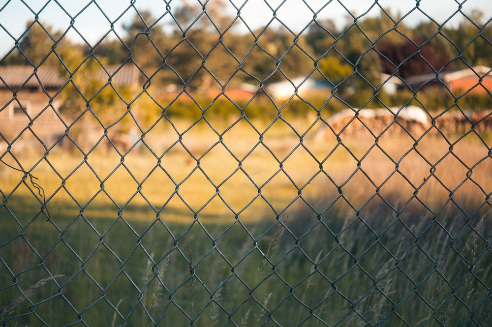green metal fence near brown field during daytime