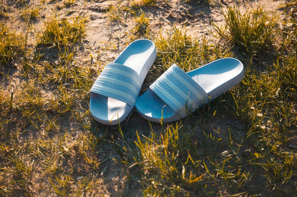 blue and white slide sandals on brown grass