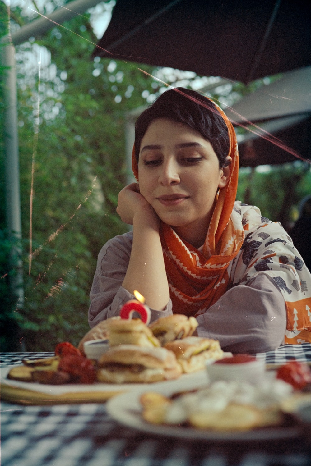woman in white and brown long sleeve shirt eating burger