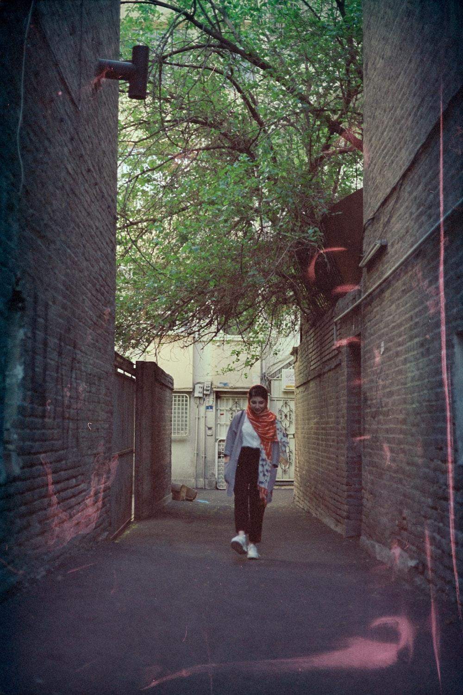 man in white shirt walking on sidewalk during daytime