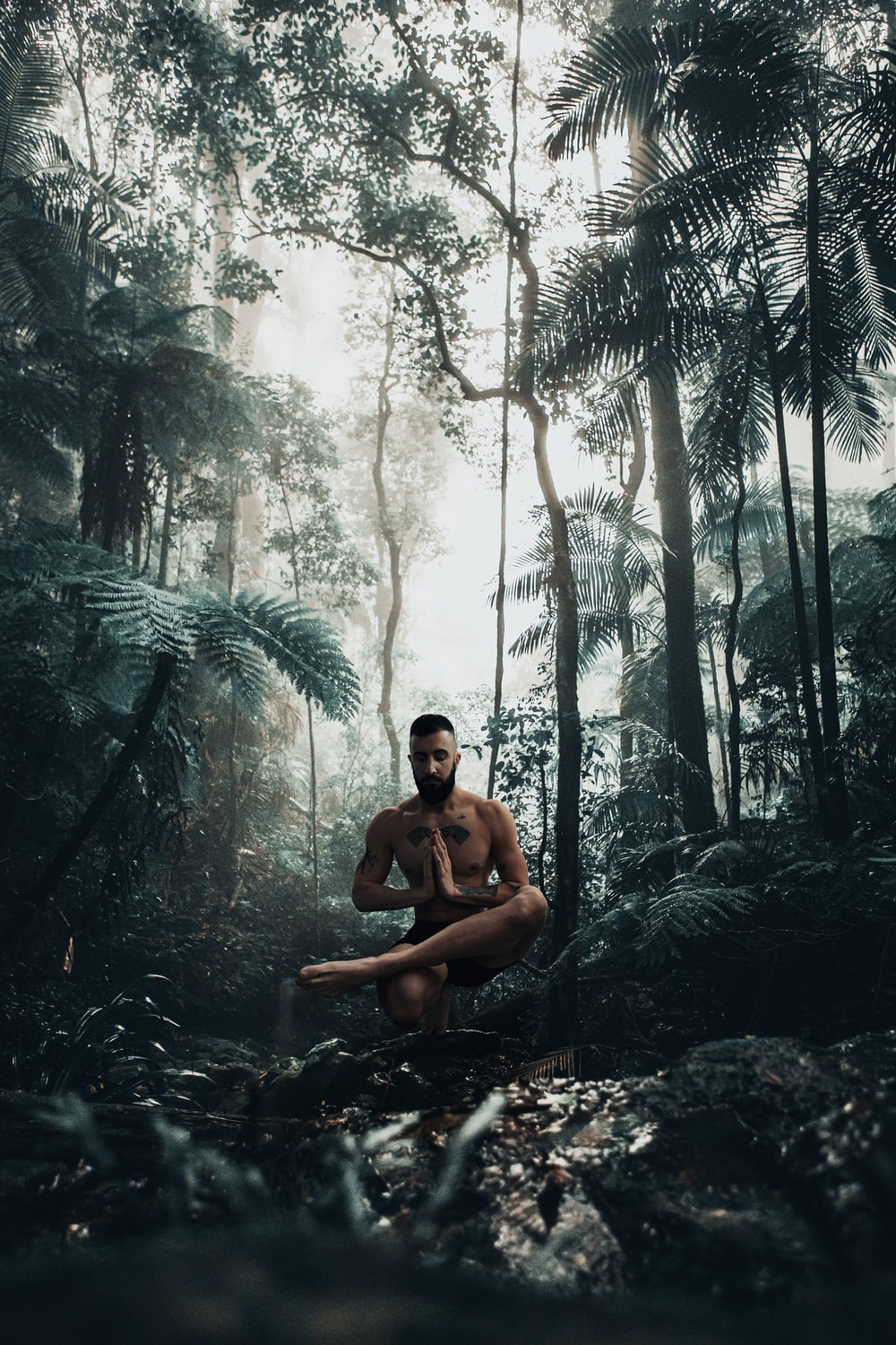 topless man sitting on rock in the middle of forest during daytime
