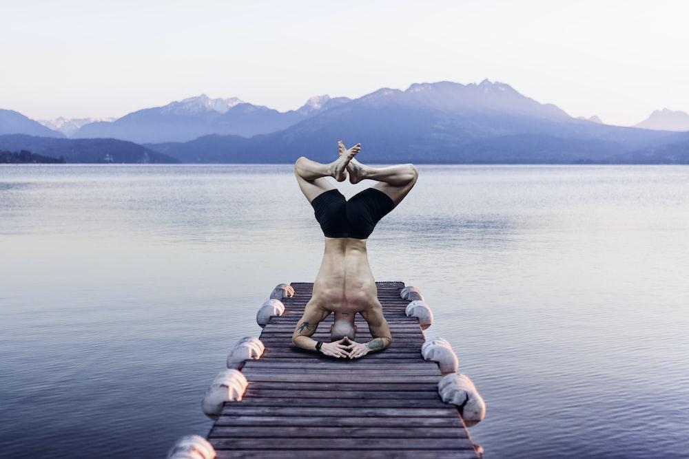 woman in black bikini sitting on dock during daytime