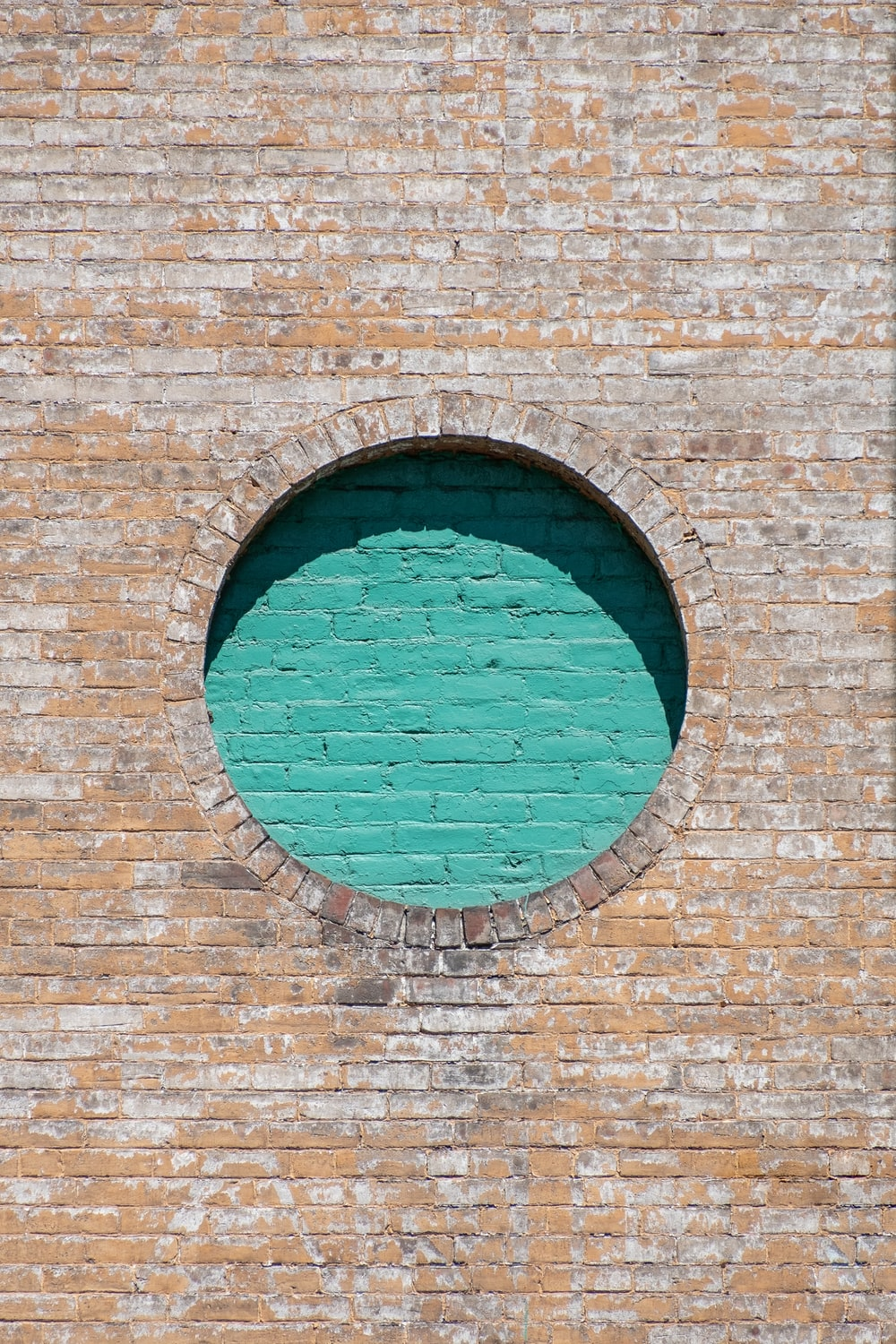 brown brick wall with blue round glass window